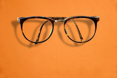 Hipster Retro fashion glasses on orange background Royalty Free Stock Photography
