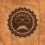 Hipster's badge on brown crumbled textured paper background Stock Photography