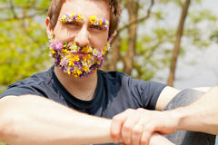 Hipster self-confident man flowers covered face Stock Photography