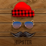 Hipster. Set of elements: a cap with a checkered pattern, glasses, mustache, on a wooden background Stock Images