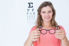 Hipster showing glasses next to an eye test Stock Photo