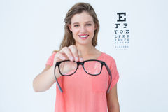 Hipster showing glasses next to an eye test Royalty Free Stock Images