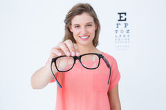 Hipster showing glasses next to an eye test Royalty Free Stock Image
