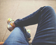 A hipster sitting downtown with crossed legs on a sidewalk bench Stock Images