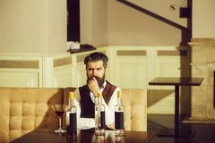 Hipster sitting on sofa with martini glass and three bottles. Man with beard drinking wine in restaurant. Alcohol abuse. Addictive and convive. Unhealthy royalty free stock photography