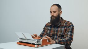 Hipster man typing with a red vintage typewriter. Hipster sitting at table and typing with a red vintage typewriter stock footage