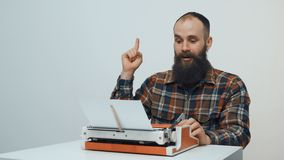 Hipster man typing with a red vintage typewriter. Hipster sitting at table and typing with a red vintage typewriter thinking and pointing a finger up hitting an stock video