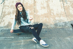 Hipster skateboarder girl with skateboard outdoor sitting at skatepark Stock Image