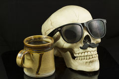 Hipster Skull and Coffee. Skull wearing Hipster glasses and a mustache, having a cup of coffee Stock Photo