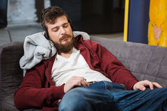 Hipster sleeping and listening music. Handsome exhausted hipster sleeping and listening music lying on sofa Stock Photos