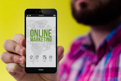 Hipster smartphone with online marketing on the screen. Online marketing concept: Hipster with beard and checked shirt holding a 3d generated smartphone with royalty free stock photography