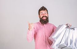 Hipster on smiling face recommends to buy. Man with beard and mustache carries bunch of shopping bags, grey background royalty free stock photography