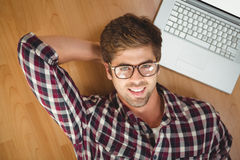 Hipster smiling while lying by laptop on hardwood floor Royalty Free Stock Image