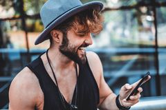 Hipster smiling and reading message Stock Photos