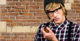 Hipster smoking pipe against brick wall Royalty Free Stock Photo