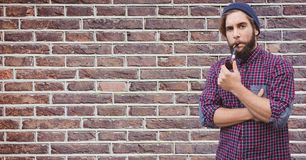 Hipster smoking pipe against brick wall. Digital composite of Hipster smoking pipe against brick wall Stock Images