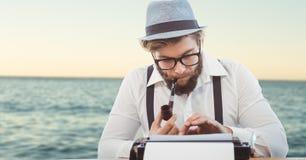 Hipster smoking pipe while using typewriter against sea. Digital composite of Hipster smoking pipe while using typewriter against sea Royalty Free Stock Image