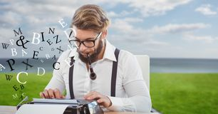 Hipster smoking pipe while using typewriter by flying letters. Digital composite of Hipster smoking pipe while using typewriter by flying letters Royalty Free Stock Photos