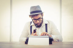 Hipster smoking pipe while working in office Royalty Free Stock Images