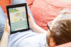 Hipster on the sofa with car sharing tablet. Technology social drive, travel and tourism concept: hipster on the sofa with car sharing app on a tablet. Screen Stock Photo