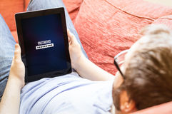 Hipster on the sofa with password tablet Royalty Free Stock Image