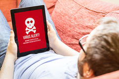 Hipster on the sofa with virus alert on a tablet Stock Images