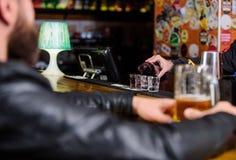 Hipster som kopplar av på baren Mannen spenderar fritid i mörk bar Mannen sitter på stångräknaren i bar Helglivsstil _ arkivbilder
