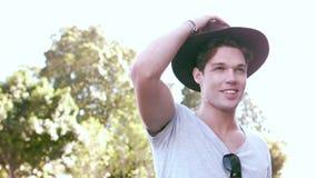 Hipster som ler mannen som tar bort hans hatt lager videofilmer