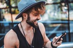 Hipster som ler och läser meddelandet arkivfoton