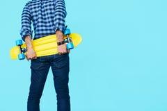 Hipster som rymmer hans skateboard med kopieringsutrymme arkivfoto