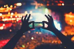 Hipster som tar foto och video på konserten Modern livsstil med smartphonen och partier royaltyfri fotografi