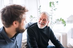 Hipster son and his senior father at home. Two generations indoors, having fun stock photos
