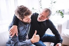 Hipster son with his senior father at home. Two generations indoors, having fun stock photos
