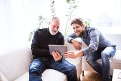 Hipster son and his senior father with tablet at home. Two generations indoors, having fun royalty free stock images