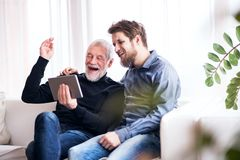 Hipster son and his senior father with tablet at home. Two generations indoors, having fun royalty free stock image