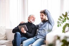 Hipster son and his senior father with tablet at home. Two generations indoors, having fun royalty free stock photo
