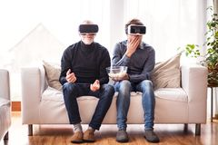 Hipster son and his senior father with VR goggles at home. Two generations indoors, eating popcorn royalty free stock photos