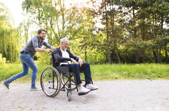 Hipster son running with disabled father in wheelchair at park. Young hipster son running with disabled father in wheelchair at park, having fun together. Carer Stock Photo