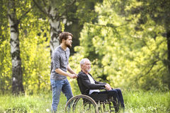 Hipster son walking with disabled father in wheelchair at park. Royalty Free Stock Image