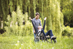 Hipster son walking with disabled father in wheelchair at park. Young hipster son walking with disabled father in wheelchair at park, having fun together. Carer Stock Photography