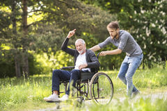 Hipster son walking with disabled father in wheelchair at park. Young hipster son walking with disabled father in wheelchair at park, having fun together. Carer royalty free stock photos