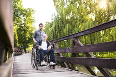 Hipster son walking with disabled father in wheelchair at park. Young hipster son walking with disabled father in wheelchair on wooden bridge at park. Carer royalty free stock photo