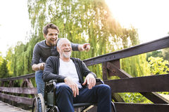 Hipster son walking with disabled father in wheelchair at park. Young hipster son walking with disabled father in wheelchair on wooden bridge at park, pointing royalty free stock image