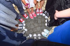 Hipster standing with sneakers in circle on concrete ground. Top view of cool youth white, black, red and pink gym shoes standing Royalty Free Stock Photo
