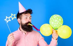 Hipster with star shaped glasses blows into party horn. Surprise concept. Guy in party hat with holiday attributes. Celebrates. Man with beard on surprised face Royalty Free Stock Photography