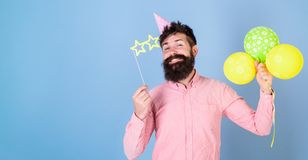 Hipster in star shaped glasses celebrates birthday. Party attributes concept. Guy in party hat with air balloons