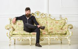 Hipster on strict face sits alone. Rich and lonely concept. Owner of luxury apartment sits on sofa, white wall. Background. Man with beard and mustache spends royalty free stock photos