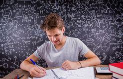 Hipster student doing his homework against a big blackboard Stock Images