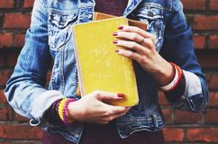Hipster student girl with bracelet and red nails holding books Royalty Free Stock Images