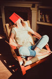 Hipster student napping in comfortable modern chair with paper book on face. Natural light. Bright sunny day. Knowledge and learni Stock Images